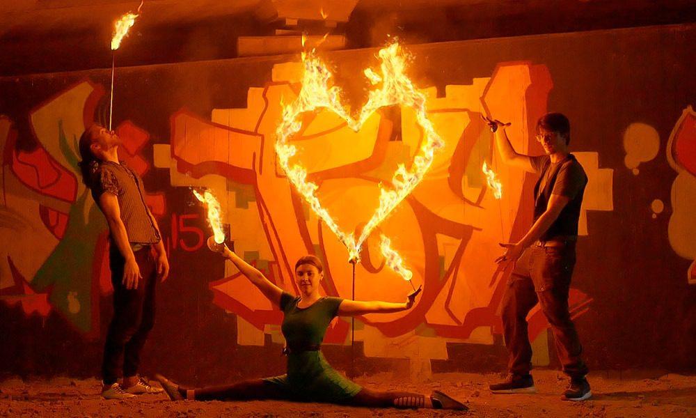 Trio Feuershow aus Stuttgart buchen - Feuerkünstlerin macht Spagat, Feuerkünstler balanciert Fackel auf der Nase und tanzt mit Feuer